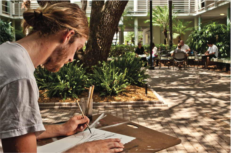Male student drawing in ASSAF courtyard.