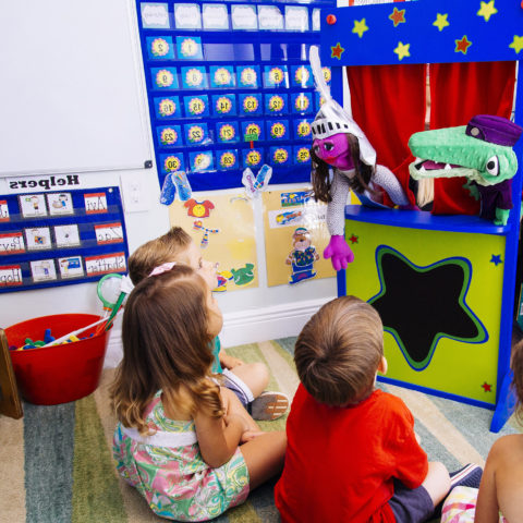 Early childhood education class putting on a puppet show for young children.