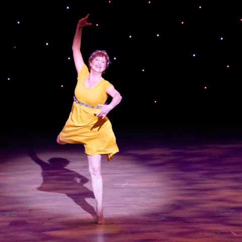 Becky Timms dances onstage in a yellow dress during Celebration of the Arts 2019.