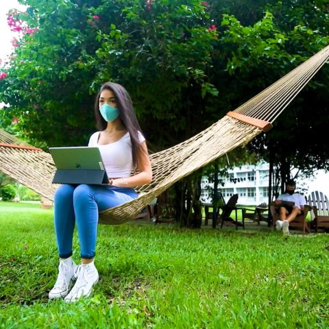 A student wearing a mask sits on a hammock and w要么ks 上 her laptop
