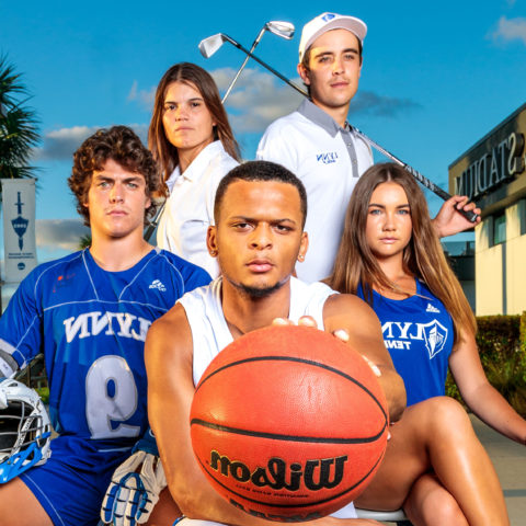 Five student-athletes strike a power pose together.